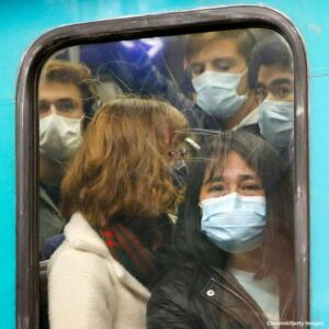 Passengers wearing protective face masks are seen riding a subway train at Con
