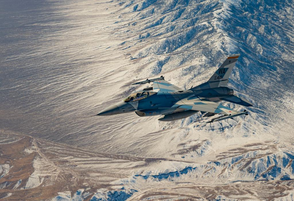 You are currently viewing An F-16 Fighting Falcon flies over the Nevada Test and Training Range. The aircr